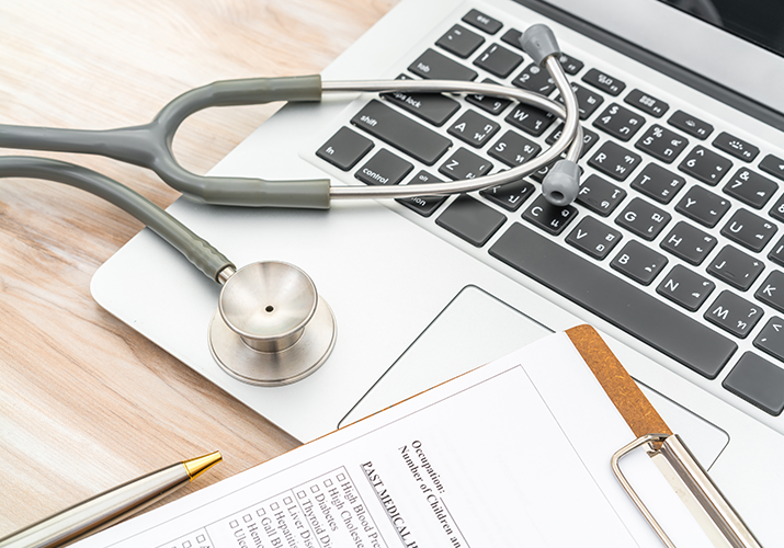 laptop keyboard with stethoscope pen and clipboard