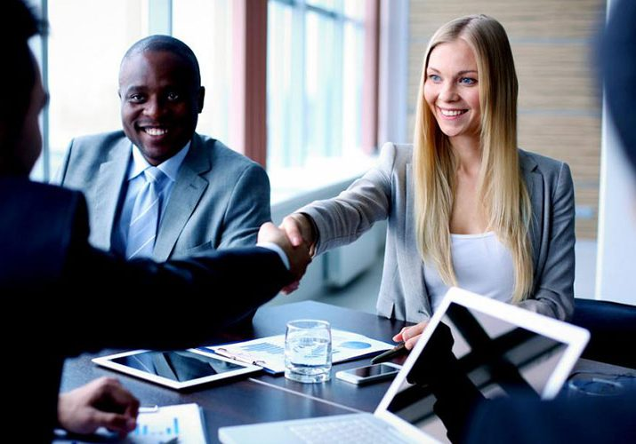 business meeting with woman reaching across to shake man's hand and second man smiling with laptop and ipad on table